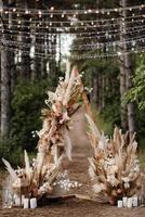 Hochzeitszeremoniebereich mit getrockneten Blumen in einer Wiese in einem Kiefernwald foto