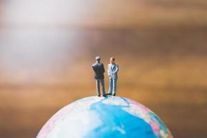 Miniaturgeschäftsleute, die auf einer Globus-Weltkarte mit einem braunen Hintergrund stehen foto