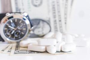 weiße Pillen und Geld auf einem weißen Hintergrund foto