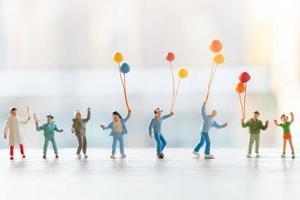 Miniaturmenschen, die mit Luftballons gehen, glückliches Familienkonzept foto