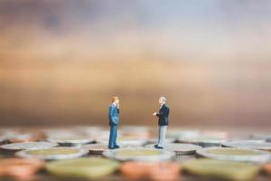 Miniaturgeschäftsleute, die auf Geld mit einem hölzernen Hintergrund stehen