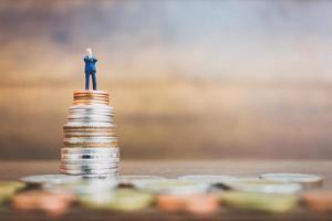 Miniaturgeschäftsmann, der auf Geld mit einem hölzernen Hintergrund steht