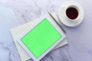 flache Zusammensetzung der digitalen Tablette und der Kaffeetasse auf Marmorhintergrund foto