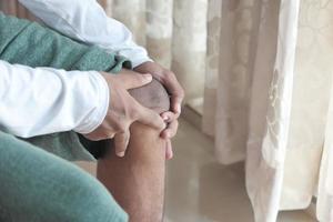 Nahaufnahme auf Mann, der Knie vor Schmerzen hält