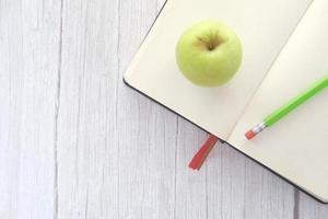 Apfel in einem Notizblock auf dem Tisch