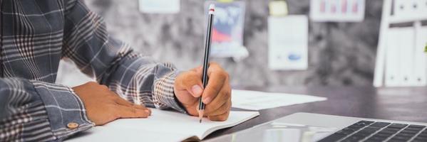 Geschäftsmann, der auf Notizbuch schreibt und plant und Informationen auf Laptop sucht foto