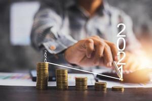Geschäft im Jahr 2021, Geschäftsmann, der auf Pfeilgraph auf gestapeltem Münzkonzept zeigt foto