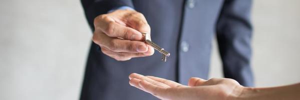 Bankagent gibt jungem Paar nach erfolgreichem Vertrag Wohnungsschlüssel foto