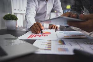 Gruppe von Geschäftsleuten, die mit einem Finanzdiagramm planen und analysieren foto