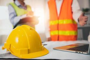 gelber Helm des Bauarbeiters auf Besprechungstisch foto