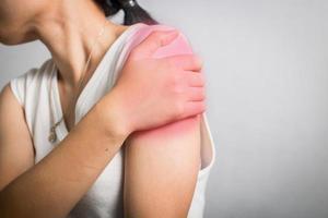Frau bekommt Schulterschmerzen von verletzten Muskeln foto