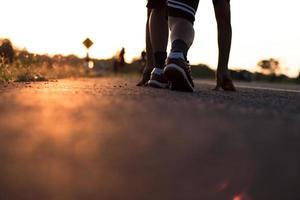 Läufer laufen auf der Straße mit Sonnenaufgang foto