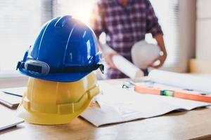 Konstruktionssicherheitshelme auf Tisch mit Ingenieur, der Blaupausenhintergrund hält foto