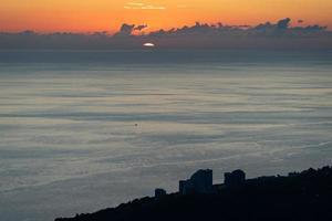 orange bewölkter Sonnenuntergang über dem Meer in Sotschi, Russland foto