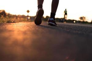 Läufer auf der Straße mit Sonnenaufgang foto
