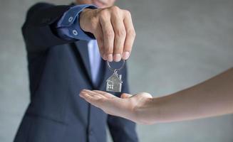 Bankagent gibt dem Käufer den Hausschlüssel foto