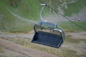 Skiliftbank oder Stuhl auf einem Kabel mit einem Berg im Hintergrund foto