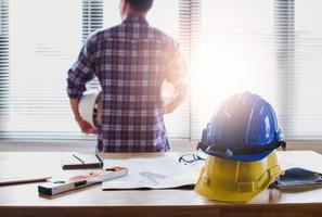Architekt oder Ingenieur, der im Hintergrund mit Helm auf Tisch arbeitet foto