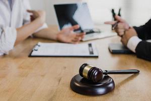 Hammer des Gesetzes auf dem Tisch mit Anwalt und Geschäftsmann foto