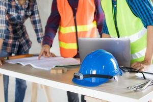 Ingenieurteam, das an Blaupausen arbeitet und plant und Informationen auf dem Laptop sucht foto
