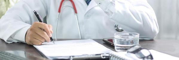 Nahaufnahme des Arztes, der Krankheitssymptome nach der Untersuchung und Behandlung des Patienten schreibt foto