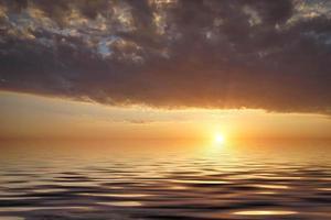 Seelandschaft mit buntem bewölktem Sonnenuntergang über dem Meer foto