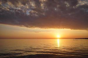 bunter bewölkter Sonnenuntergang über einem Gewässer