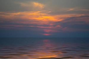 dunkelorange bewölkter Sonnenuntergang über einem Gewässer