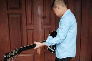 Junge hält eine Gitarre foto