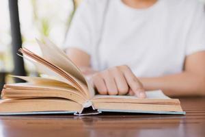 Studentin liest Buch auf dem Schreibtisch und bereitet sich auf den Test vor foto