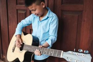 Junge, der Spaß daran hat, Gitarre zu spielen foto