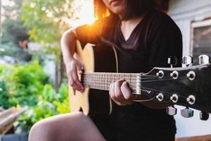 Frau spielt eine Akustikgitarre foto