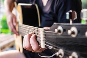 Nahaufnahme einer Person, die eine Gitarre spielt foto