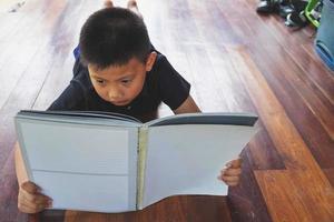 Junge liest auf dem Boden foto