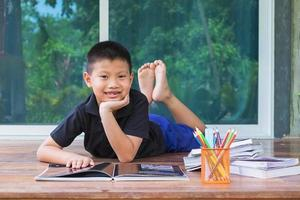 Junge posiert mit Lernmaterialien foto