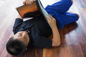 Junge legt sich beim Lesen hin foto