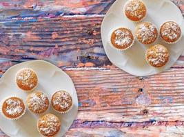 Muffins auf zwei weißen Tellern auf einem hölzernen Tischhintergrund foto