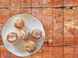 Muffins auf einem weißen Teller auf einem hölzernen Tischhintergrund foto