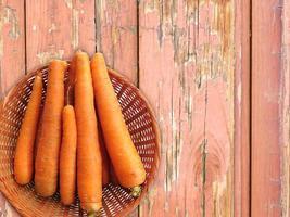 Karotten in einem Weidenkorb auf einem hölzernen Tischhintergrund foto