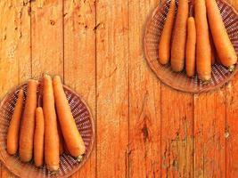 Karotten in zwei Weidenkörben auf einem hölzernen Tischhintergrund foto