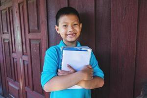 Junge umarmt Bücher foto