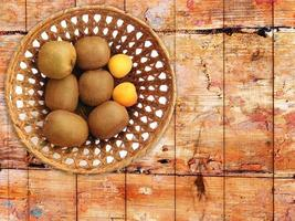 Kiwis und Aprikosen in einem Weidenkorb auf einem hölzernen Tischhintergrund foto