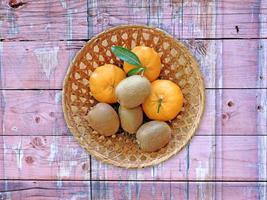 Kiwis und Orangen in einem Weidenkorb auf einem hölzernen Tischhintergrund foto