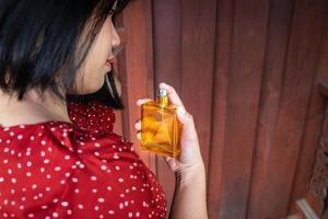Frau sprüht Parfümflasche foto