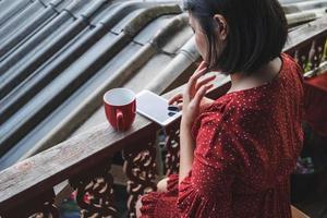 Frau sitzt mit einem Kaffee und Telefon auf einer Terrasse