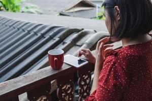 Frau am Telefon mit einem Kaffee