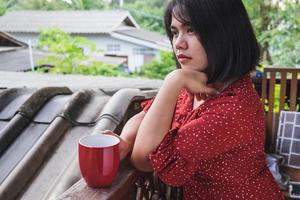 Frau sitzt mit einem Kaffee auf einer Terrasse