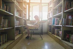 Junge liest im Sonnenlicht foto