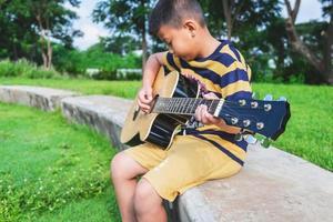 Junge spielt eine Gitarre in einem Park foto
