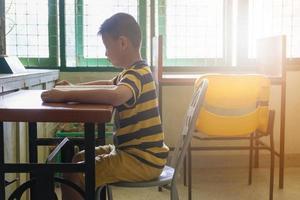 Junge liest an einem Schreibtisch foto